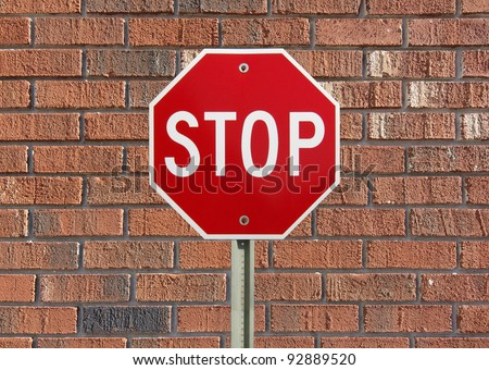 Stop sign up against a brick wall