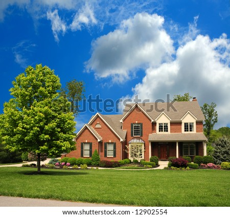 2-Story Brick Suburban Home on a sunny summer day.