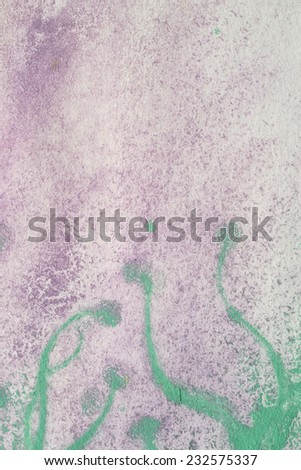 streaks of green paint on paint purple with a round end