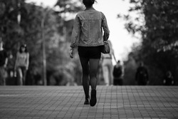 Street photo. girl walks in the park. black and white photo. Concept photo
