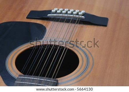 12 string guitar closeup of soundhole and bridge looking down against a white background