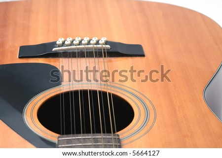 12 string guitar closeup of soundhole, bridge and lower body against a white background