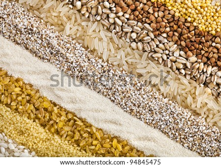striped rows of dry groats , couscous, bulgur, grain ,cereal,buckwheat, rice, backdrop