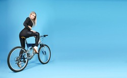 studio shot of a sportive woman sitting on a bicycle on blue background with copy space. beautiful young woman wearing sportswear posing with a bike in a photo studio