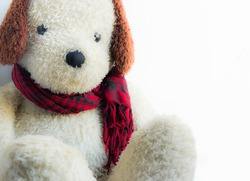Stuffed dog tied red plaid scarf.