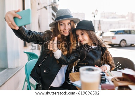 Stylish family sitting in a city cafe look in the phone and take selfies and smile on the sunny city background. Little girl show finger to the top looking at camera. True emotions,  good mood.