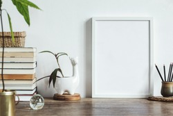 Stylish interior design of kitchen space with small table with mock up frame, books, avocado plant , lama pot and cup with pencils. Minimalistic interior.
