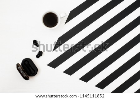 Stylish minimalistic workspace with cup of coffee, wireless earphones isolated on striped black and white background. Flat lay style Top view.  #1145111852