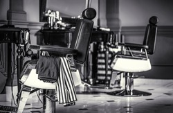 Stylish vintage barber chair. Professional hairstylist in barbershop interior. Barber shop chair. Black and white.