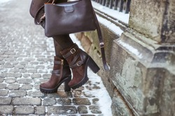 Stylish young fashionable woman with dark brown leather bag and high heel winter boots. Winter street fashion look