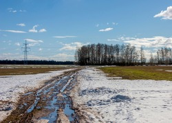 Suburbs of Grodno. Belarus. Spring landscape.Country road with unmelted snow, puddles, field, forest and blue spring sky with white clouds.