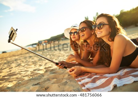 summer holidays and vacation - girls sunbathing on the beach.girls doing selfie phone.  enjoy summer time. Fun at the beach. Great summer mood. sunny day