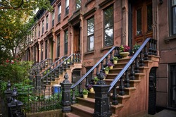 summer view of a row of stoops and historic brownstone buildings on one of the iconic streets in a neighborhood of Brooklyn in New York City.