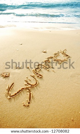 """Summer"" written in the sand beach , blue waves in the background"