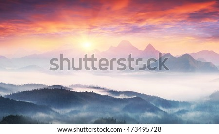 sunrise, the sun's rays illuminate the beautiful panorama of the Carpathian village against backdrop of scenic mountains, where the highlanders live Hutsul. Wild forests, fields pastures