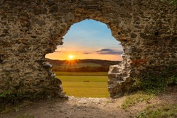 sunset and Czech landscape fields, and forests through the hole walls of the castle ruins in the Central Bohemian region from the 14th century