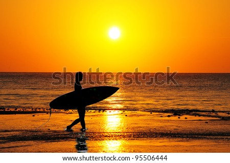 Surfer silhouette walking into the waves at sunrise