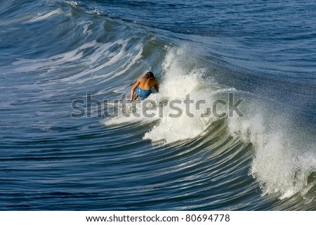 Surfing is very popular,Surfers start at the shore line and paddle their way out to where the big waves are, these young people are learning to ride