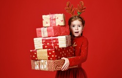 surprised funny child girl in red Christmas reindeer costume with gifts on green colored background