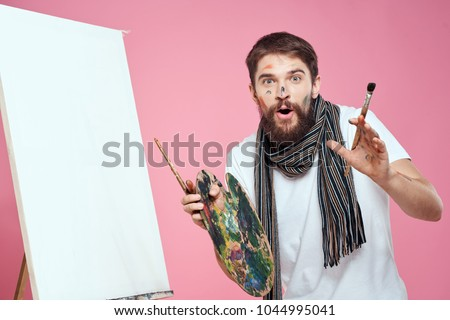 surprised painter with a paintbrush and a palette on a pink background, art, watercolor, easel