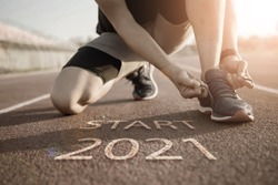 2021 symbolises the start into the new year.Start of people running on street,with sunset light.Goal of Success