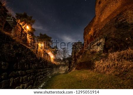 Úštěk, Czech republic - January 01 2013: A long exposure night shot of an area between walls and former palace of Helfenburk (Hrádek) castle, lit by torches. Starry New Year night. #1295051914