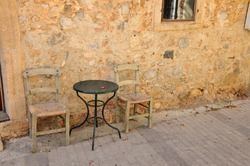table and chairs against a yellow wall, in Greece