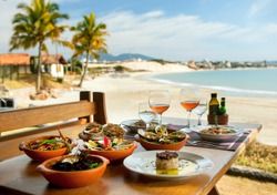 table with seafood dishes with beach background