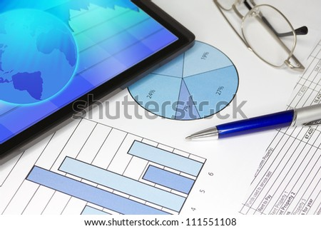 Tablet Computer in ipade style with Blue Pen Spectacles Figures and Graphs