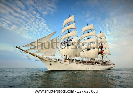Tall Ship under sail with the shore in the background