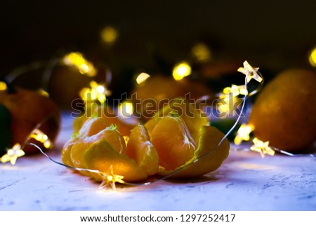 Tangerines. Natural tangerines with green leaves and twinkled stars on the white background.Slice of a peeled tangerine #1297252417