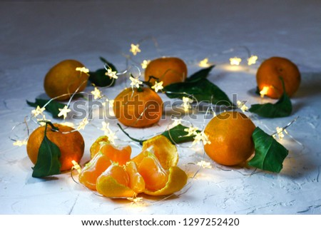 Tangerines. Natural tangerines with green leaves and twinkled stars on the white background.Slice of a peeled tangerine #1297252420