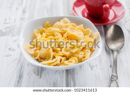 tasty corn flakes with milk and cup of coffee on white Rustic wooden background. Healthy crispy breakfast snack.
