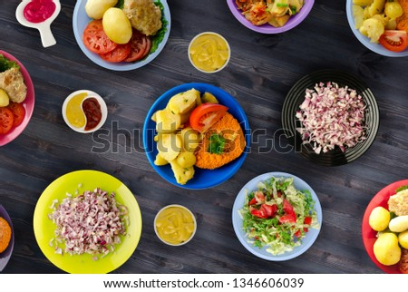 Fried pork chop, baked potatoes and vegetable salad Images