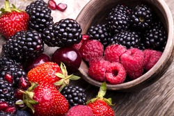 tasty summer fruits on a wooden table. Cherry, Blue berries,  strawberry, raspberries, Blackberries, pomegranate