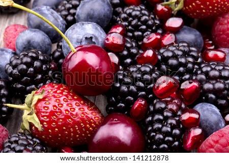 tasty summer fruits on a wooden table. Cherry, Blue berries,  strawberry, raspberries, Blackberries, pomegranate #141212878