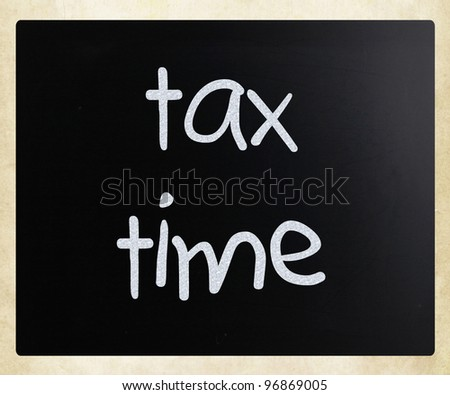 """Tax time"" handwritten with white chalk on a blackboard"