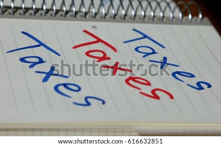 """Taxes"" written onto note pad in blue and red color in handwriting  #616632851"