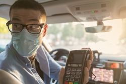 Taxi driver wearing glasses and mask to protect himself from coronavirus hands a payment terminal to a customer