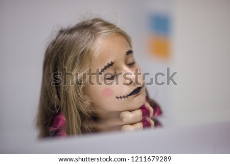 7 tear old girl with painted face, puts on Halloween makeup, looking herself in mirror. Reflection portrait. Depth of field, white bathroom background. One hand on face. Beautiful child. Kids fashion. #1211679289