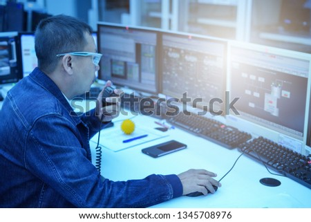 Technical Controller checking the process of power plant monitor.                #1345708976