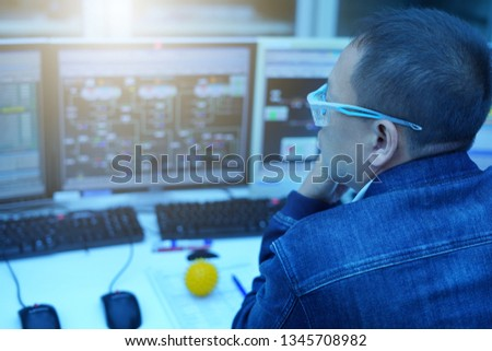 Technical Controller checking the process of power plant monitor.                #1345708982