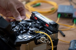 technician welding optical fiber cable with fusion splicing fiber optic Machine., pad cot cable