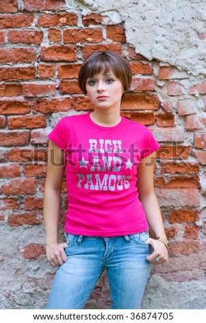 teen girl next to brick wall