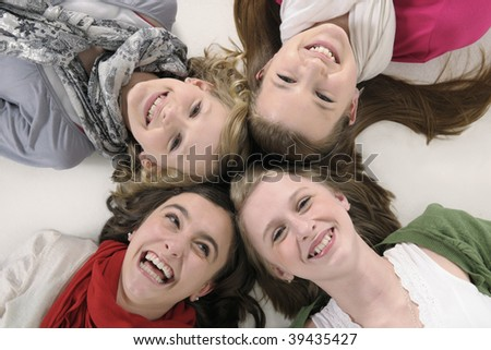 4 teenage girl friends lying down and smiling up at camera