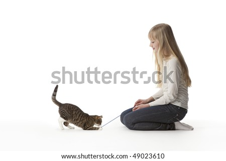 Teenage girl is playing with her cat at white background