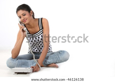 Teenage girl sitting on the floor talking over telephone
