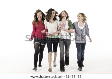 4 teenage girls linking arms walking towards camera smiling