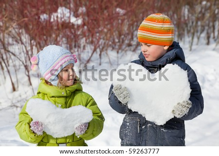 teenager boy and little girl keeps in hands hearts from snow in winter in wood
