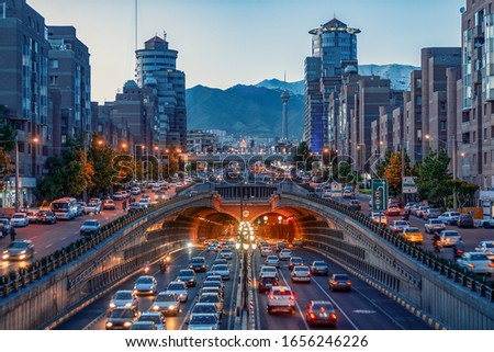 Tehran,Iran,Famous night view of Tehran,Flow of traffic round Tohid Tunnel with Milad Tower and Alborz Mountains in Background, Tohid Tunnel one of longest urban tunnel in Middle East Stock fotó ©